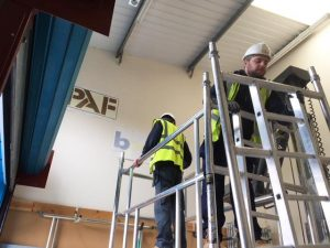 Men wearing tabards and hard hats working at height
